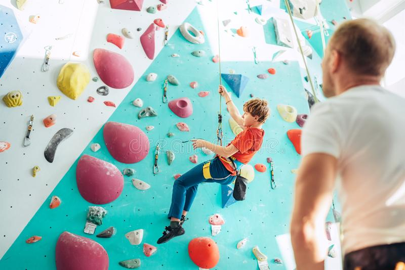 Father and teenager son at indoor climbing wall hall. Boy is hanging on the rope using a climbing harness and daddy belaying him. On the floor using a belay royalty free stock image