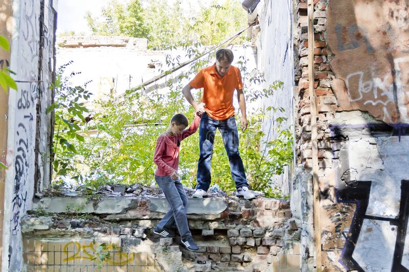 Father and son are playing through ruins. Father and teenager son are playing in ruins royalty free stock image