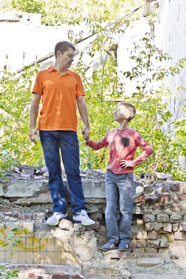 Father and son are playing through ruins. Father and teenager son are playing in ruins royalty free stock photo