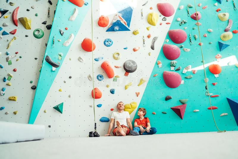 Father and teenager son sitting near the indoor climbing wall. They resting after the active climbing. Happy parenting concept stock images