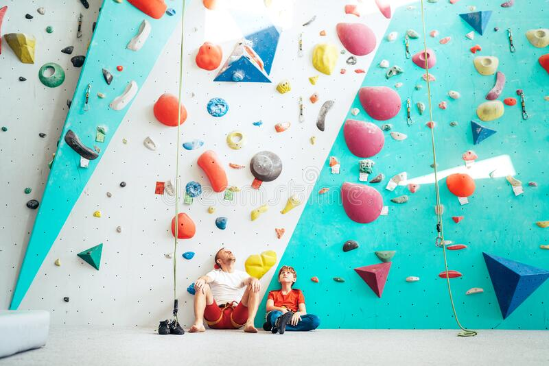 Father and teenager son sitting near the indoor climbing wall. They resting after the active climbing. Happy parenting concept. Image royalty free stock photography