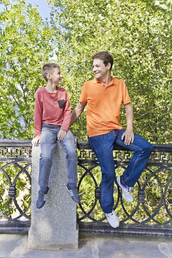 Father and teenager son together. Father and son are talking and looking to each others in summer royalty free stock image