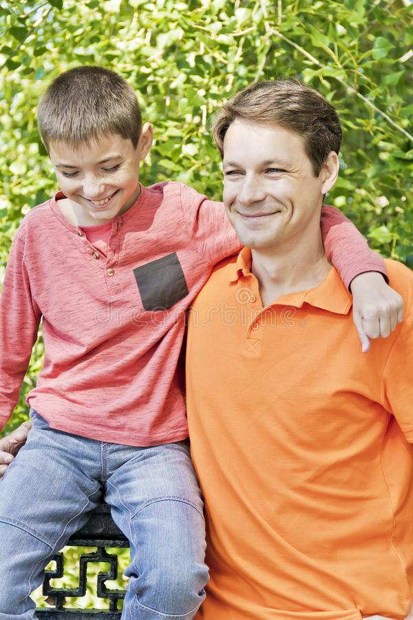Father and teenager son together. Father and son are talking to each others in summer royalty free stock photos