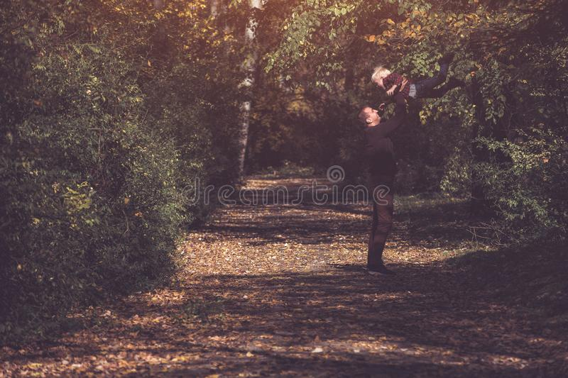 Father throws up his blond son. Happy childhood. Autumn forest stock image