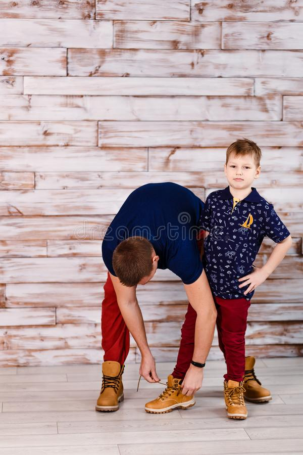 Father ties shoelaces on son`s shoes royalty free stock image
