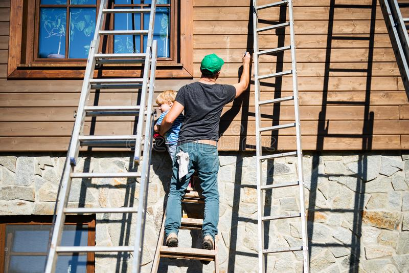 A father and toddler boy outdoors in summer, painting wooden house. royalty free stock photos