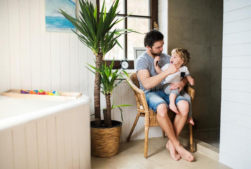 Father and a toddler boy sitting on a chair and brushing their teeth at home. Father and a toddler boy sitting on a chair and brushing their teeth in the stock photography