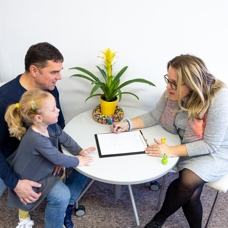 Father and toddler daughter in therapist office during counselling meeting. stock image