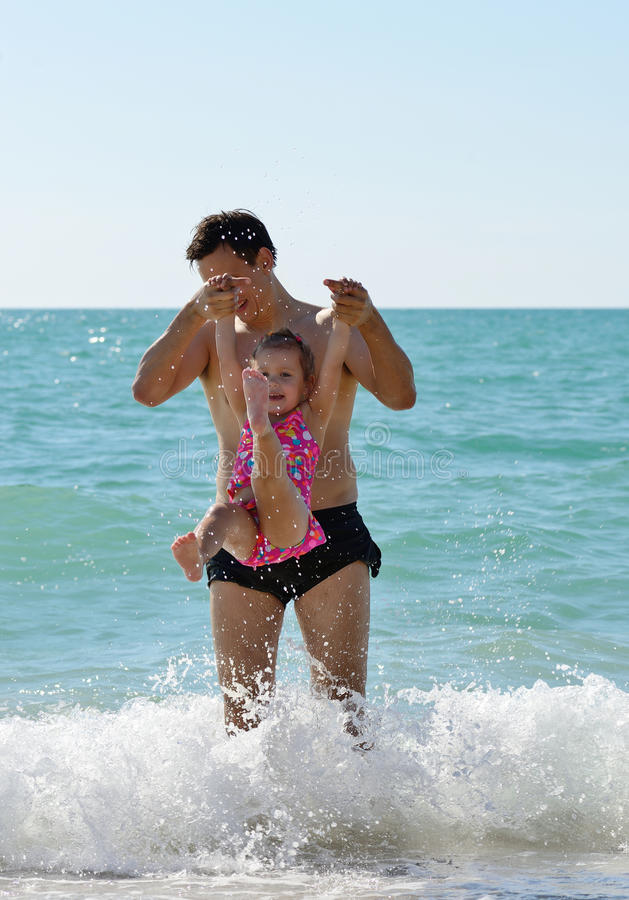 Father and toddler girl in sea stock images