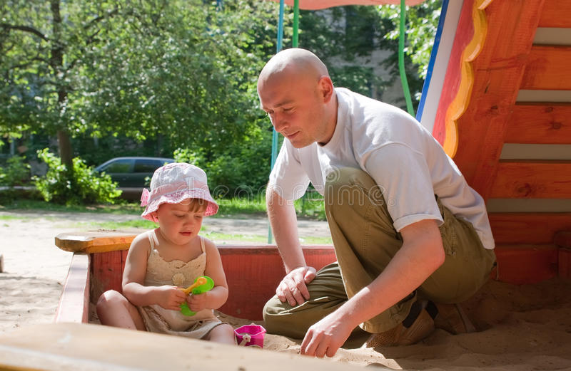 Father with toddler playing in sandbox stock photo