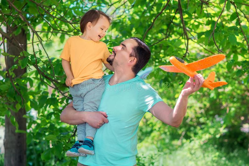 Father and son playing together with orange airplane outdoors: boy is sitting on shoulder of man, both dad and kid are smiling stock photo