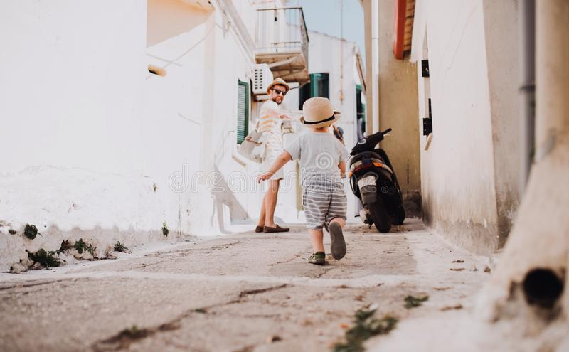 A father with toddler son walking in town on summer holiday. royalty free stock photos