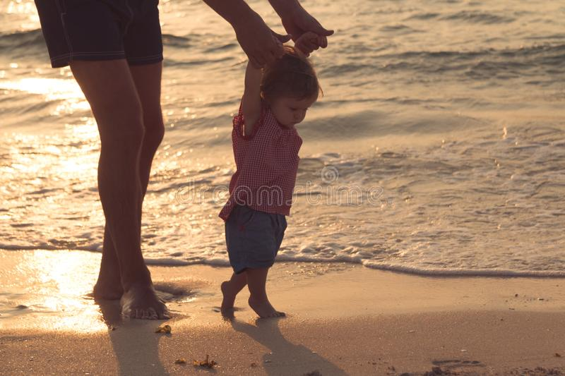 Father took the baby learn to walk at sunset. stock image