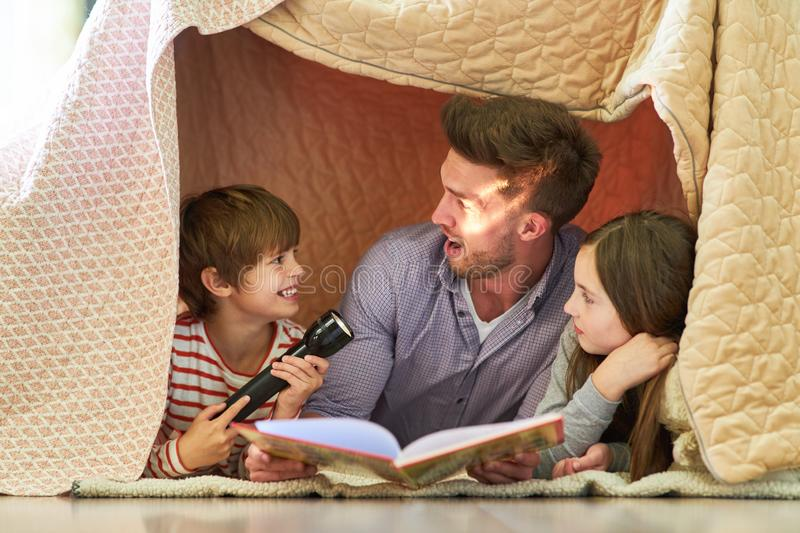 Father and children with flashlight reading aloud royalty free stock image