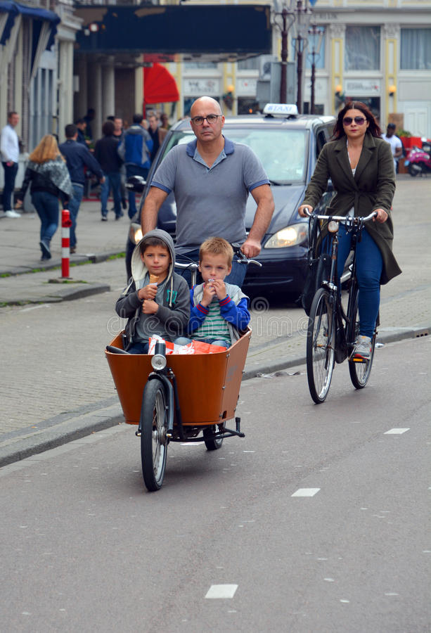 Father with two children riding bicycles stock photo