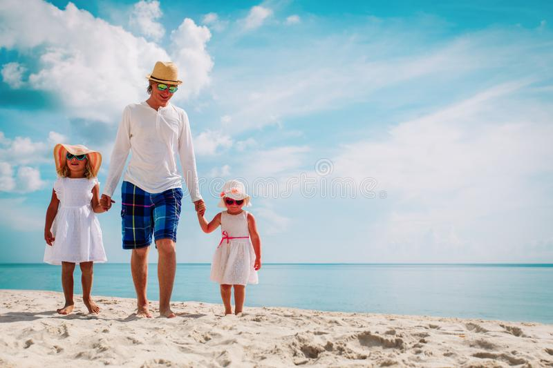Father with two cute daughter walking on beach royalty free stock photos