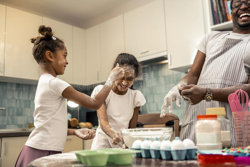 Father and two cute daughters having much fun while cooking pie. Having much fun. Loving father and two cute daughters having much fun while cooking pie stock images