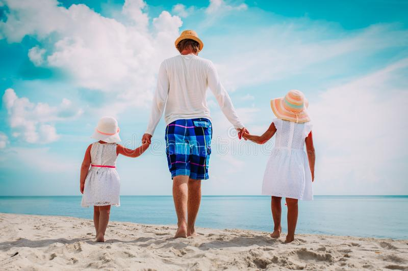 Father with two daughter walking on beach royalty free stock photos