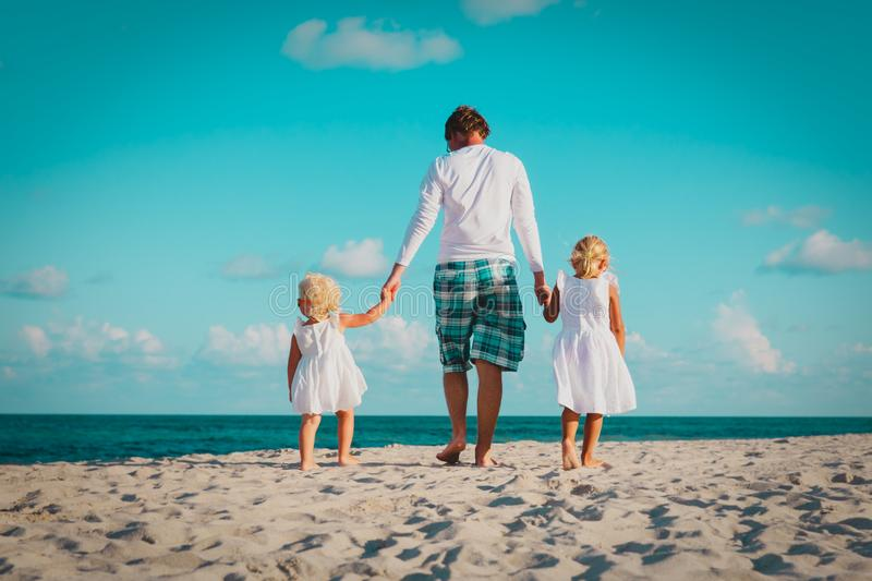 Father with two daughter walking on beach stock photo