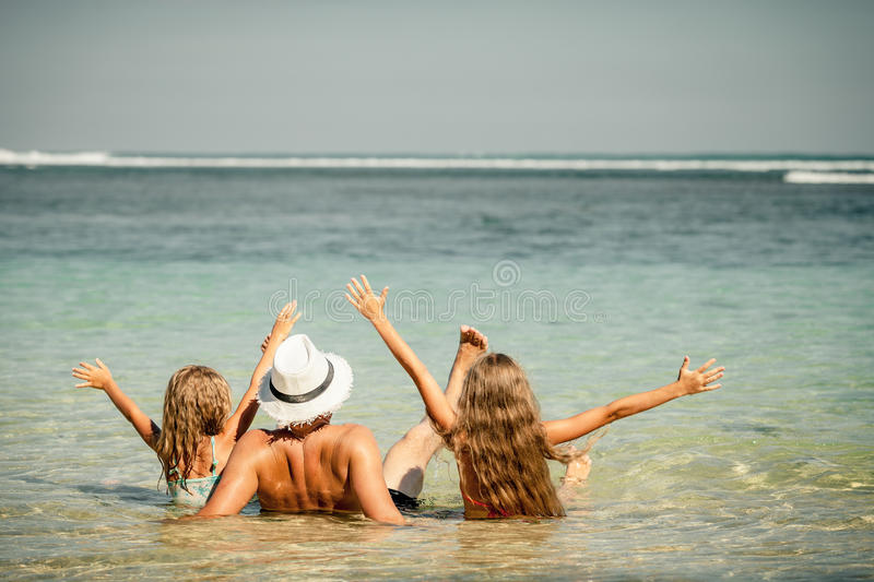 Father and two daughters sitting at the beach royalty free stock images