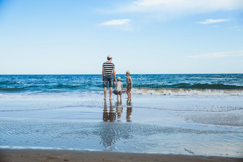 father and two daughters standing at the beach stock photography
