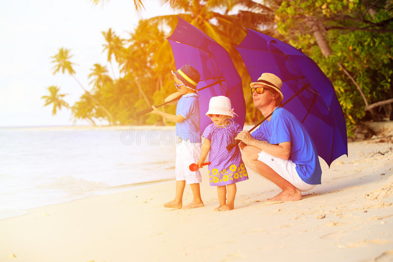 Father and two kids at beach with umbrellas stock photo