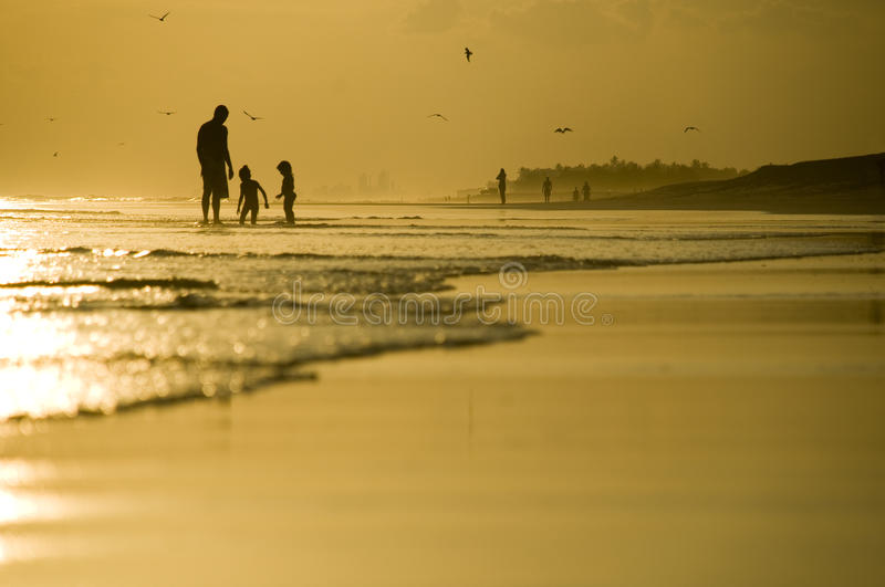 Father and two kids playing on the beach. During sunset royalty free stock images
