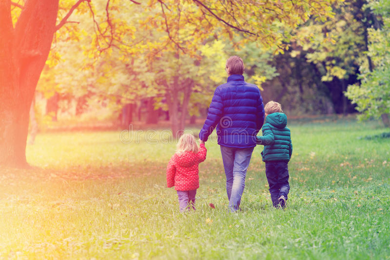 Father with two kids walking in autumn fall stock photos