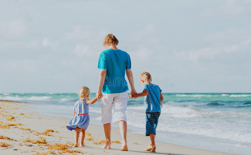 Father and two kids walking on beach stock photography