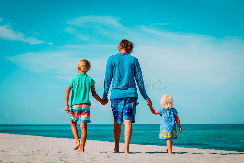 Father and two kids walking on beach stock image