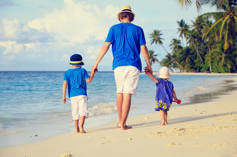 Father and two kids walking on summer beach royalty free stock image