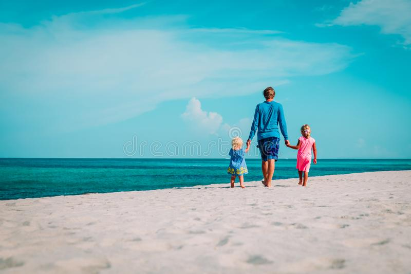 Father with two little daughters walking on beach royalty free stock images