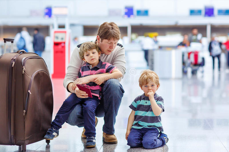 Father and two little sibling boys at the airport. Tired father and two little sibling kids boys at the airport, traveling together. Upset family waiting stock images