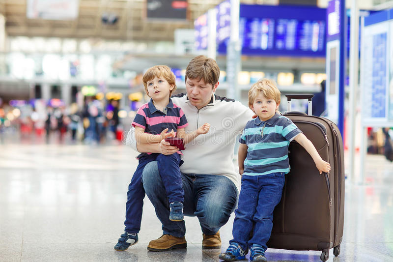 Father and two little sibling boys at the airport. Tired father and two little sibling kids boys at the airport, traveling together. Upset family waiting royalty free stock photo