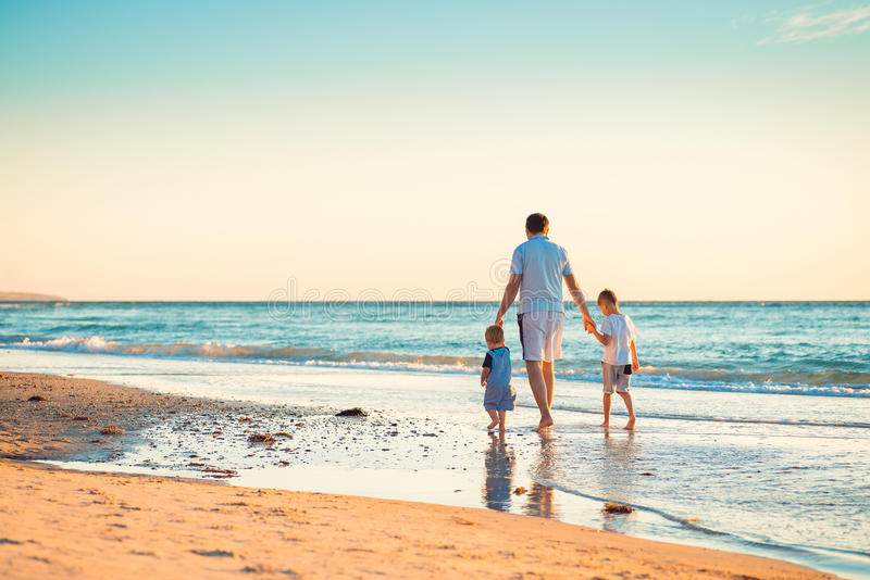 Father with two sons walking on beach stock photo