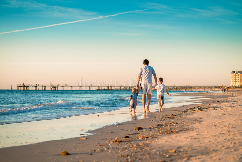Father with two sons walking on beach royalty free stock images