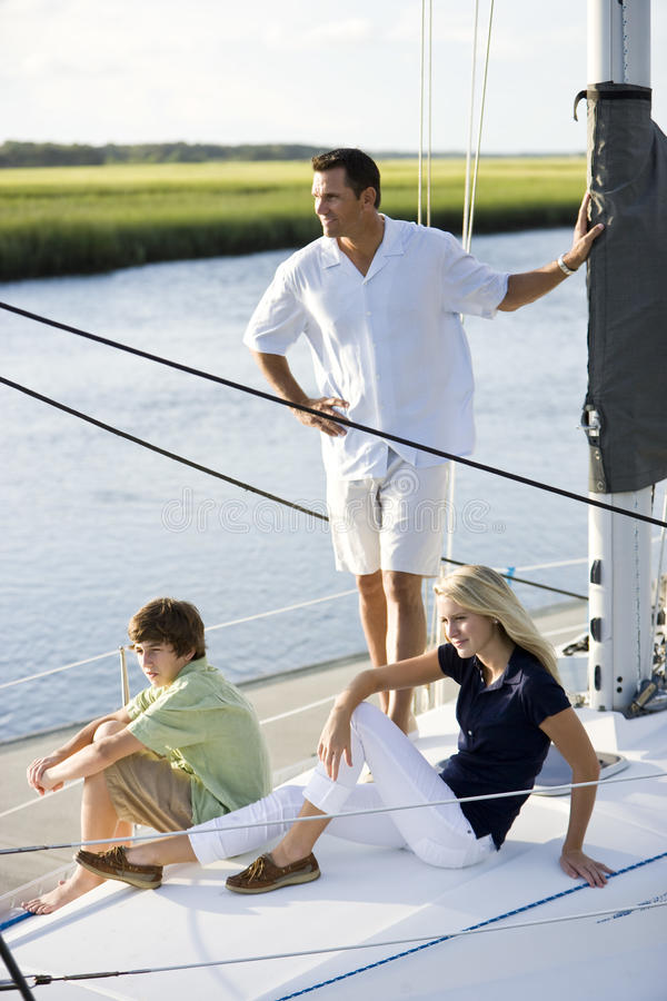 Father and two teenage children relaxing on boat stock photography
