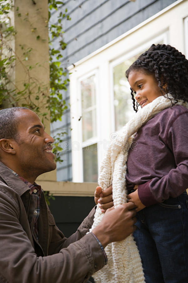 Father tying daughters scarf royalty free stock photo