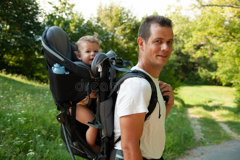 Father on a walk with kik in child carrier backpack stock photos