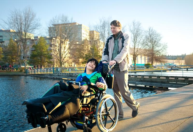Father walking with disabled son in wheelchair at lake park stock images