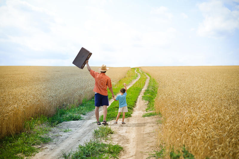 Father walking with his son on the road in royalty free stock photography
