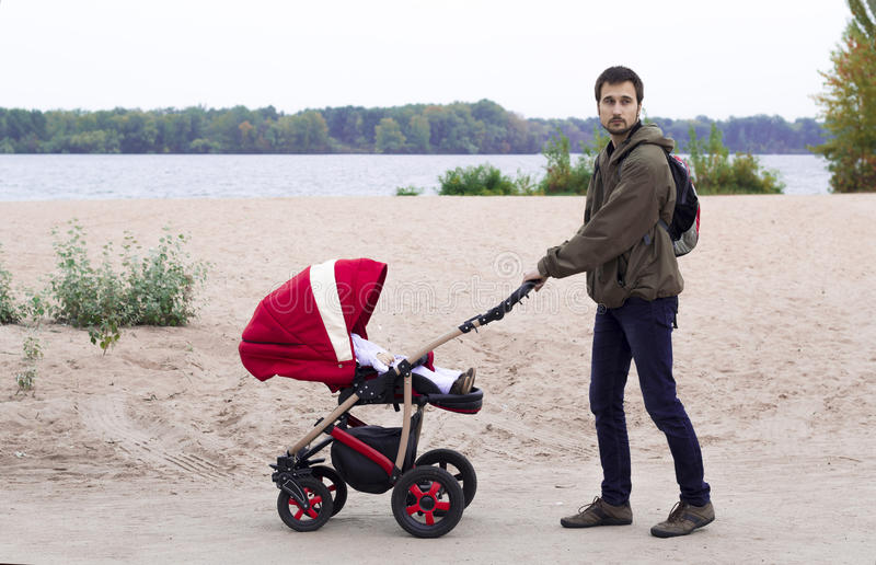 The father walks with baby in the baby carriage in the park royalty free stock photos