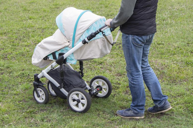 Father walks with carriage, bottom view only legs. Bright mint stroller and legs in jeans, walking with a child outdoor stock images