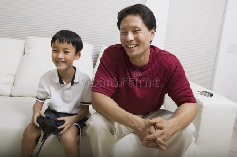 Download Father Watching Son Play Video Game On Couch Stock Photo - Image of side, parent: 13584386