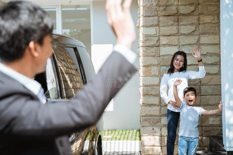 father waving goodbye to his family before going to work royalty free stock photography