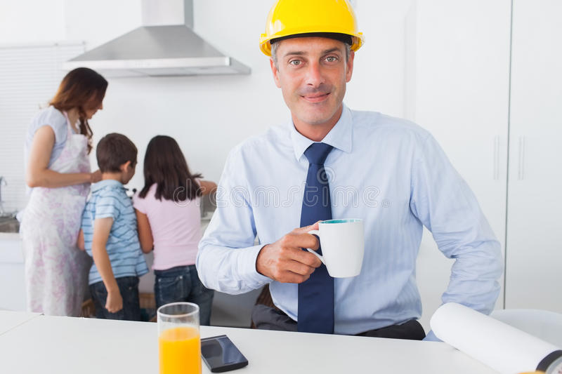 Father wearing hardhat and drinking coffee at home with his family. In the kitchen before work stock image