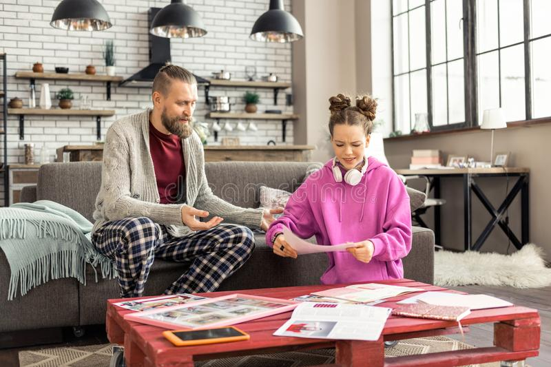 Father wearing pajamas trousers watching his girl doing homework stock image