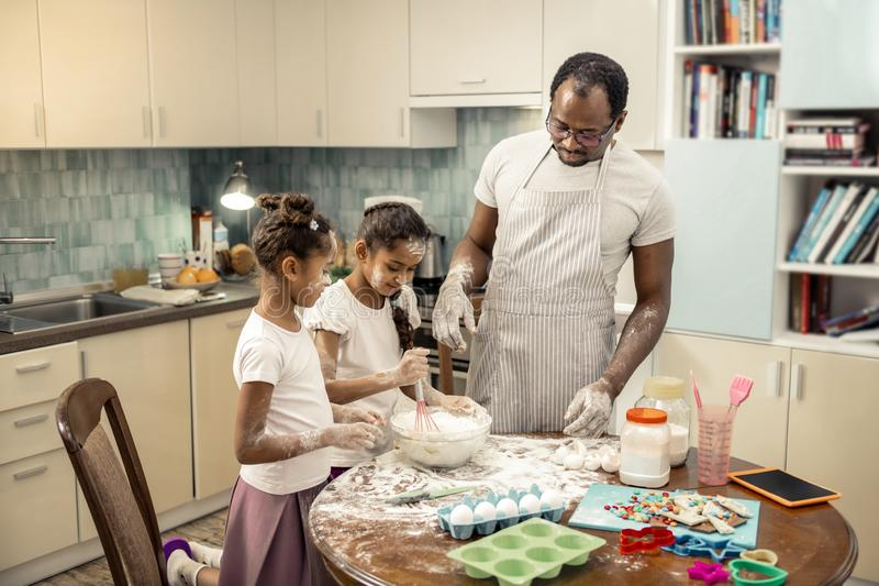 Father wearing striped apron assisting daughters cooking cupcakes. Assisting daughters. Dark-haired father wearing striped apron assisting his daughters cooking royalty free stock image