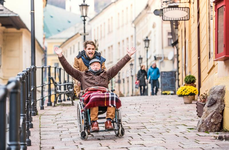 Senior father in wheelchair and young son on a walk. stock photo