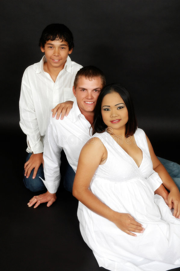 Father, pregnant mother and son. Pose together in close knit group on a dark background stock photography